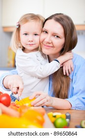 Young mother and her adorable little daughter making salad