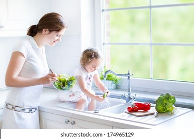Young mother and her adorable toddler daughter cooking salad together in a beautiful white kitchen with a big garden view window