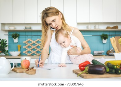 Young mother with her baby daughter in a modern kitchen setting. Young attractive cook woman desperate in stress, tired.