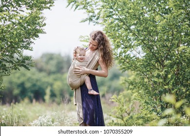 A young mother with her baby girl in a sling in a field. Concept of green parenting