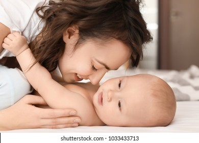 Young mother and her baby on bed at home
