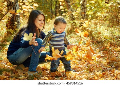 a young mother with her baby outdoor. playing mom and son in an autumn park
