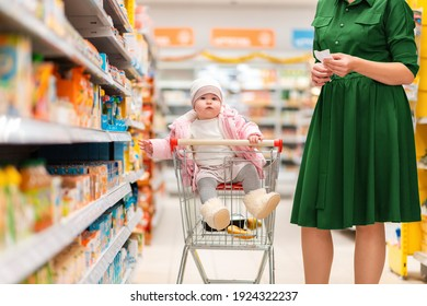 A young mother and her baby sitting in a grocery cart choose food on a supermarket shelf. Side view. Close up. The concept of shopping and parenting.