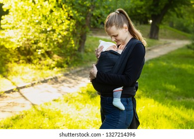 A young mother with her baby in a sling scarf is standing in a sunlight. Mom looks at the child. Wrapping sling for carrying a child.