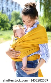 Young mother with her baby in sling walking in park