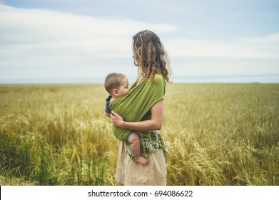 A young mother with her baby in a sling is standing in a field