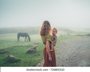 A young mother with her baby in a sling is standing in the fog looking at a horse