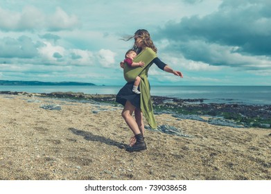 A young mother with her baby in a sling is entertaining him by spinning around on the beach