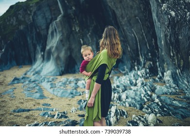 A young mother with her baby in a sling is standing by some rocks on the beach