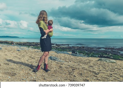 A young mother with her baby in a sling is standing on the beach