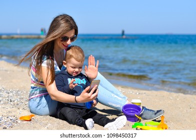 A young mother with her baby talking on a video call on the beach