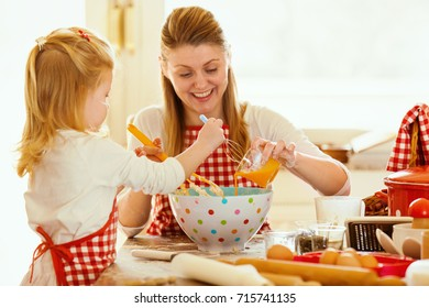 Young mother and her beautiful 4 years old daughter making dough for croissants. Lifestyle photo.