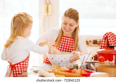 Young mother and her beautiful 4 years old daughter making dough for biscuits. Lifestyle photo.