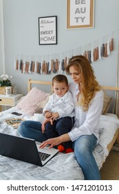 A young mother with her beloved son on bed with a laptop. Work on maternity leave at home with a child concept.
