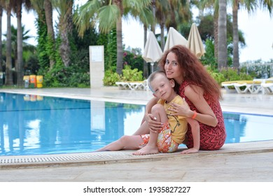 Young mother with her beloved son on the background of the pool.Summer vacation concept. Always together