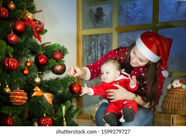 A young mother and her child are sitting on the windowsill of a snowy window near a Christmas tree decorated with toys.