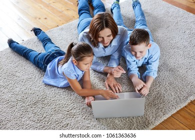 A young mother and her children behind a laptop in the living room