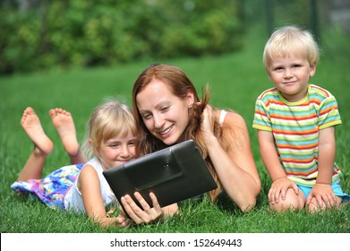 young mother with her children lie on grass and looking at screen of laptop. summer day.