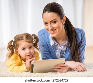 Young mother and her cute daughter are looking at laptop.