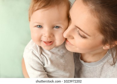Young mother with her cute little baby at home