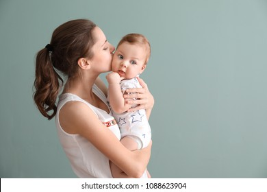 Young mother with her cute little baby on grey background