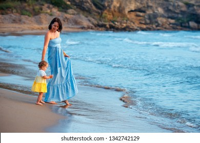 Young mother and her cute little baby girl playing on a beautiful tropical beach enjoying family summer holiday. Family sea summer vacation. Ocean and water fun for parent and kids. Fit and healthy fa