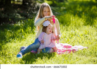 A young mother with her daughter blowing soap bubbles in the park