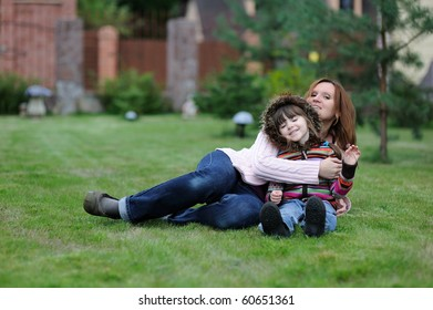 Young mother and her daughter in colorful sweaters  having fun on the grass in the garden