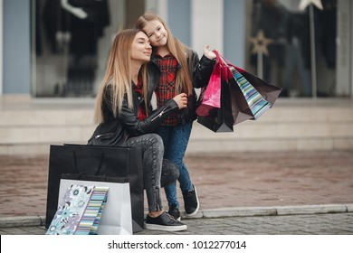 Young mother and her daughter doing shopping together. woman with girl child after shopping in street. woman with daughter with shopping bags outdoors. Woman and her daughter after shopping