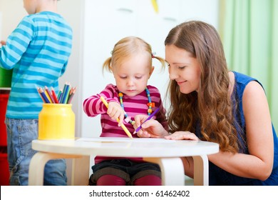 Young mother and her daughter drawing together. Also perfect for kindergarten/daycare context.