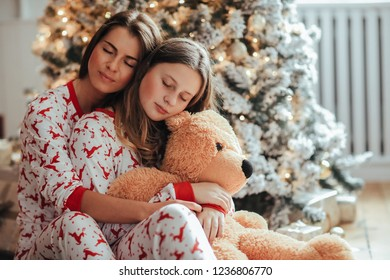 Young mother and her daughter in festive pajamas during christmas