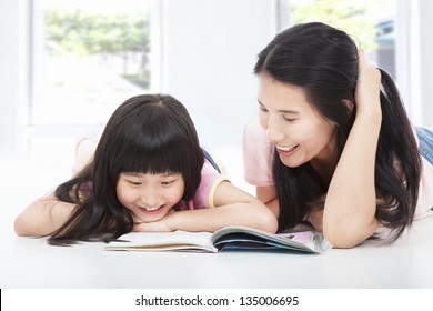 young  mother and her daughter lie on the floor and reading a book