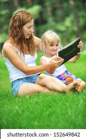 young mother with her daughter  looking at screen of laptop. summer day.