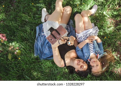Young mother and her daughter making selfie on mobile. Girls making picture on cell phone and having fun. Pretty girlfriends. Mom and her child outdoor.