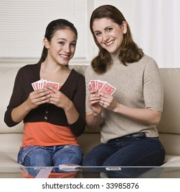 A young mother and her daughter are playing cards together.  They are smiling at the camera.  Square framed shot.