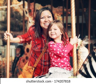 a young mother and her daughter riding on a merry go round at th