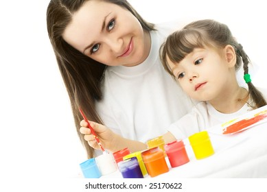 young mother and her daughter sitting by the table and painting with watercolor