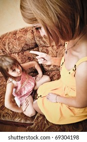 Young mother with her daughter sitting on sofa and educating