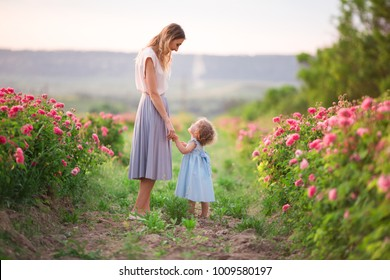 Young mother with her daughter are walking in spring garden with pink blossom roses flowers, sunset time