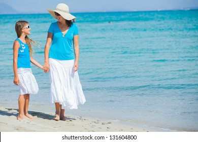 Young mother with her daughter walking on tropical beach