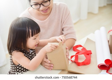 Young mother and her daughter wrapping a gift box for Birthday, Christmas and New year in a white room. Happy Asian family at the house. Copy space.