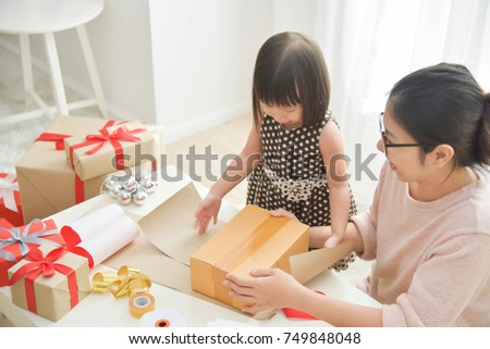 Young Mother And Her Daughter Wrapping A Gift Box For Birthday Christmas New Year