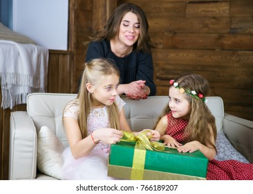 Young mother with her daughters before Christmas at the evening in cozy room