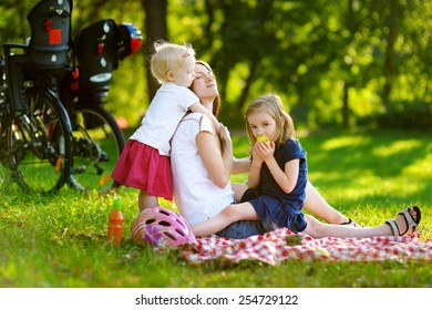 Young mother and her daughters having a picnic in the park on beautiful summer day