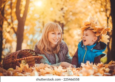 Young mother and her kid have fun in the autumn park