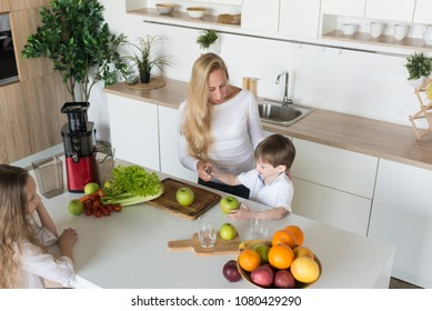 young mother and her kid son cooking and cutting fruits and vegetables in the kitchen,  making vegetable salad, chopping vegetable on cutting board with knife. Cooking concept of happy family.