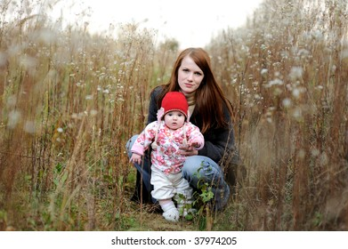 Young mother with her little baby in an autumn grass