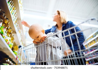 Young mother with her little baby boy at the supermarket, shopping.