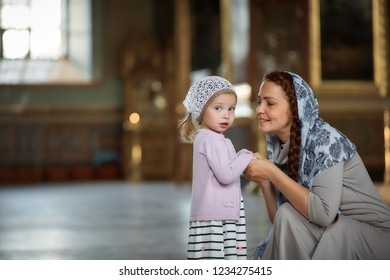 Young mother and her little blond Caucasian daughter with candles in Orthodox Russian Church