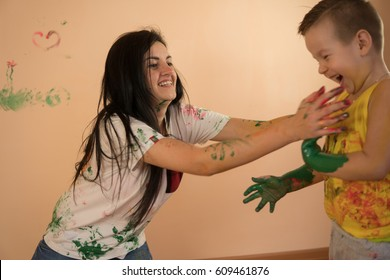 Young mother with her little boy are lmixing colors at their hands yo leave beautiful handprints on the wall. Mother and child concept